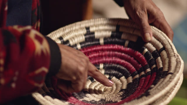 a native american (navajo) woman in her sixties discusses a woven navajo basket while touching it - north american tribal culture stock videos & royalty-free footage
