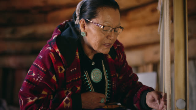 a native american woman (navajo) in her sixties weaves at a loom indoors in a hogan (navajo hut) - native american reservation stock videos & royalty-free footage