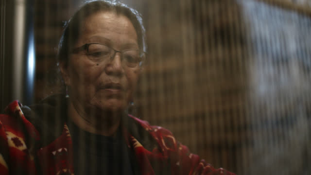 a native american woman (navajo) in her sixties weaves at a loom indoors - navajo culture stock videos & royalty-free footage
