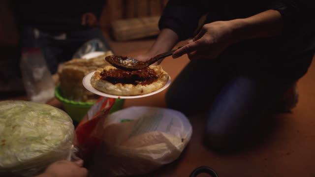 a native american (navajo) woman scoops beans on to a tortilla (fry bread) while an elderly woman talks with a man in his forties indoors at a family gathering - minority groups stock videos & royalty-free footage