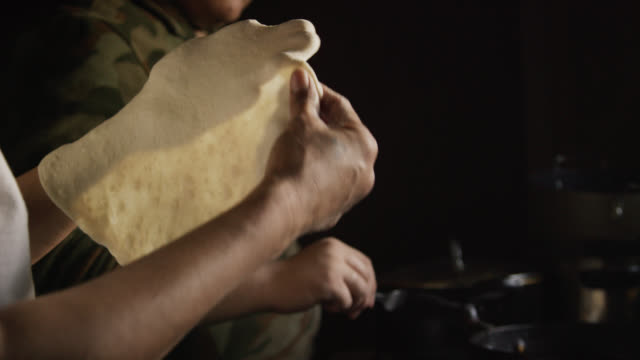 a native american (navajo) woman's hands form a raw tortilla (fry bread) while another woman removes a cooked tortilla and places it on a finished stack before placing a raw tortilla into oil on a stove indoors - navajo culture stock videos & royalty-free footage
