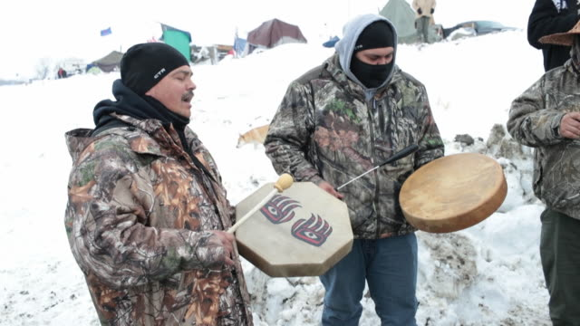 vídeos de stock e filmes b-roll de native americans from washington state drum and sing as they wait for the arrival at oceti sakowin camp of native american activists traveling from... - cultura tribal da américa do norte
