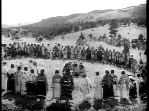 stockvideo's en b-roll-footage met montage native americans in traditional dress with teepees, sitting, dancing in a circle, drumming / united states - amerikaans indiaanse etniciteit