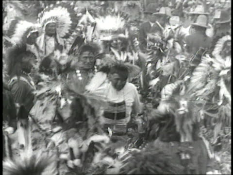stockvideo's en b-roll-footage met native americans wearing traditional clothing dance in a field and greet united states president calvin coolidge. - hoofdtooi