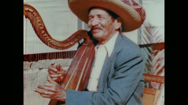 1947 native californian busks on the street smiling as he plays the harp - musicista video stock e b–roll