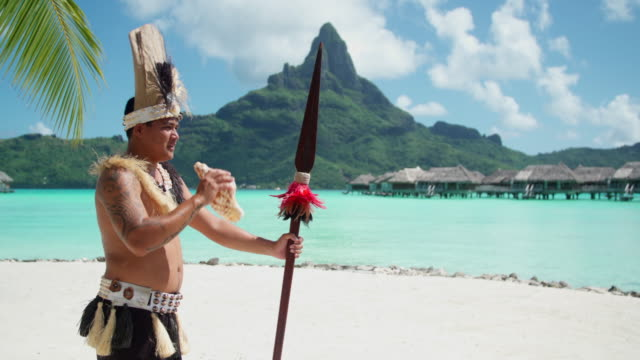 a native islander man blows a conch shell holding a ceremonial spear at a tropical island resort. - conch stock videos & royalty-free footage