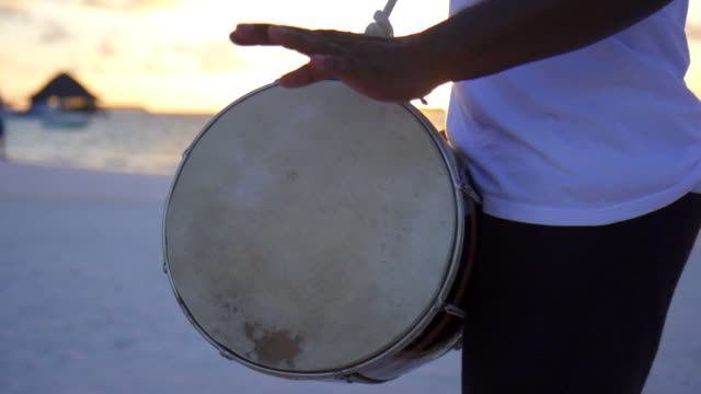 native local men play drums and music at a tropical island resort hotel. - slow motion - 太鼓点の映像素材/bロール