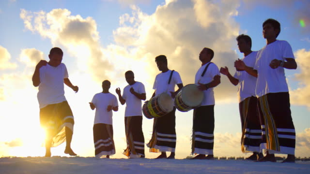 Native local men play drums, music and dance at a tropical island resort hotel.