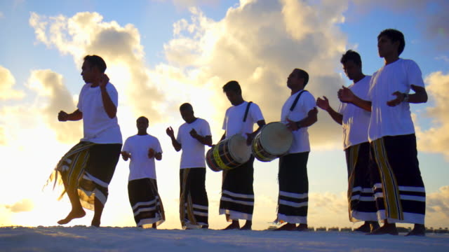 Native local men play drums, music and dance at a tropical island resort hotel. - Slow Motion