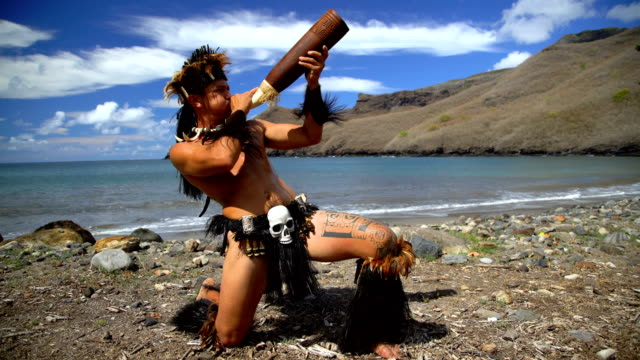 native male playing traditional horn on beach marquesas - polinesiano video stock e b–roll