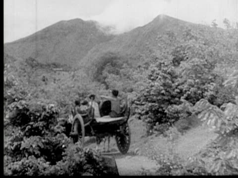 vidéos et rushes de 1930 b/w montage native men accompanying priestess along mountain road in ox carts for traditional ritual/ ws tu native men sounding a gong while climbing mountainside with priestess/ myanmar/ audio - femme dans un groupe d'hommes