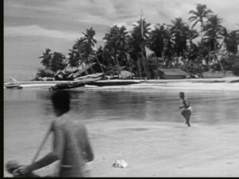 1949 B/W MONTAGE Native men throwing fishing nets from beach and catching small fish while boys watch / Likiep, Marshall Islands