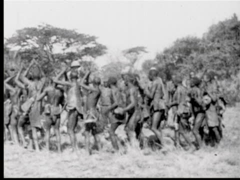 Natives dance clap in circle around dead lions white hunter