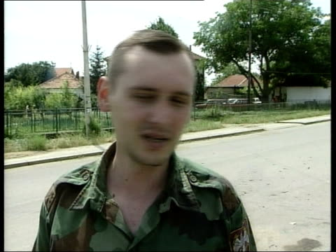 Nato troops move in/Serbs move out ITN Serbia Kosovo Decorative iron cross on church Little boy outside door of church Woman crying outside church...