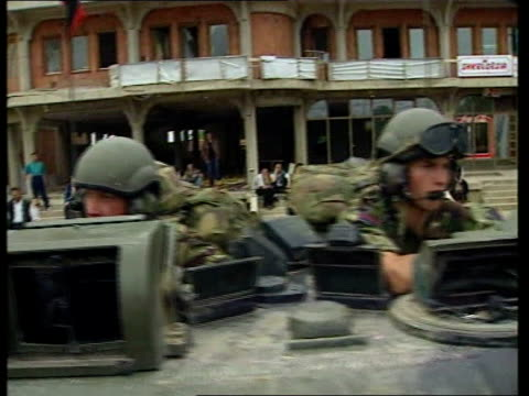 Nato troops move in/Serbs move out ITN Serbia Kosovo British Army armoured car along road PULL OUT crew of armoured car in front looking out from...