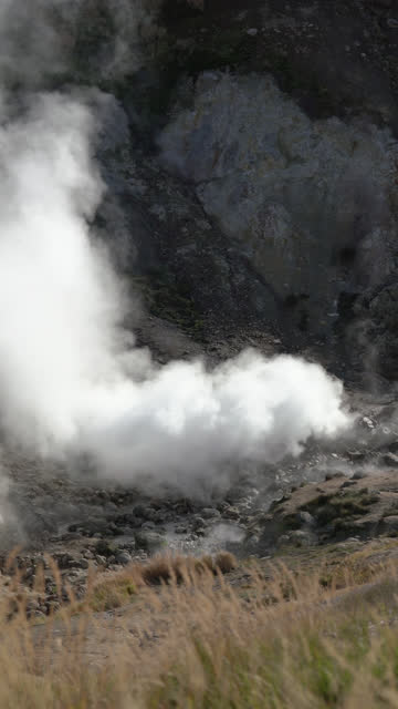 natural aggressive volcanic landscape of kamchatka peninsula - hot springs, geothermal field on active volcano. vertical format video - volcano stock videos & royalty-free footage