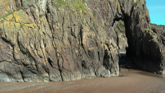 natural arch in coastal cliffs at a beach in south west scotland - natural arch stock videos & royalty-free footage