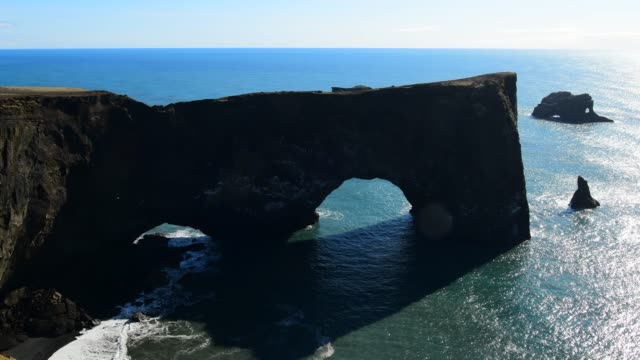 natural arch of dyrholaey peninsula - iceland - eroded stock videos & royalty-free footage