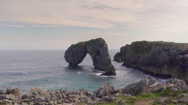 vídeos de stock e filmes b-roll de natural arch rock formation sea landscape - arco natural