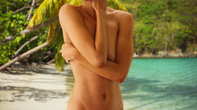 Natural black woman covering topless chest with arms and hands.  Nude sensual woman standing on beach in Virgin Islands.