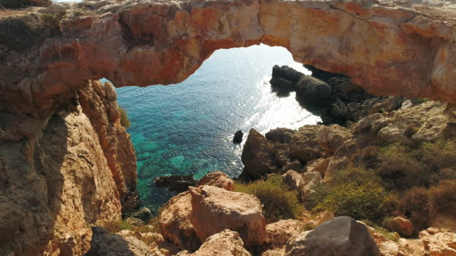 natural bridge stone arch near ayia napa, cyprus.  aerial drone shot. 4k 60fps prores - arch architectural feature stock videos and b-roll footage