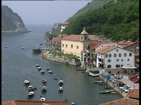 Natural harbour and opening to sea with boats moored and red roofed buildings in foreground San Sebastian