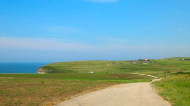 vidéos et rushes de natural landscape of coast with cliffs and sea seen from a car by the rural road - route à une voie