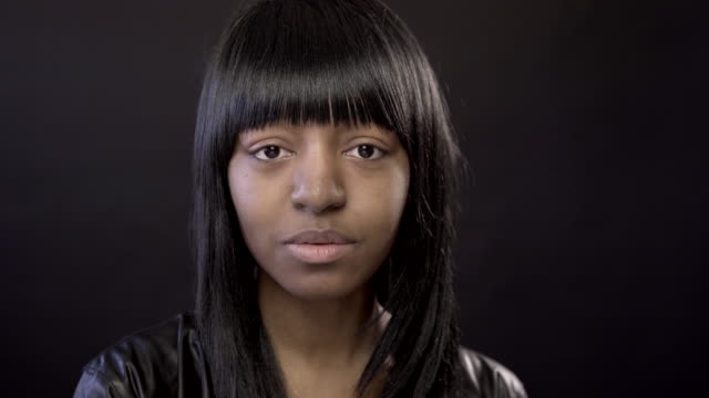 natural young black woman with no make-up on a black background - bangs stock videos & royalty-free footage