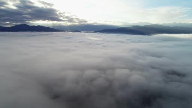 stockvideo's en b-roll-footage met natuur en cloudcscape. drone: luchtfoto over zee van wolken, sunbeam, mist en mist over de heuvels, hemel oogpunt, heldere zonnige dag, zonlicht, helder helder blauwe hemel, schoonheid in de natuur - sunny