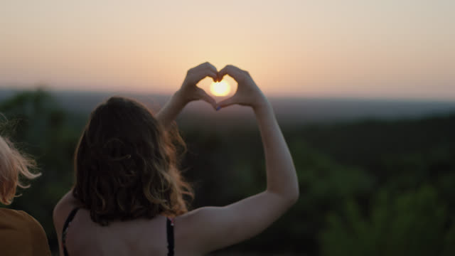 MS SLO MO. Nature girl makes heart shape with hands framing the setting sun on green mountainside.