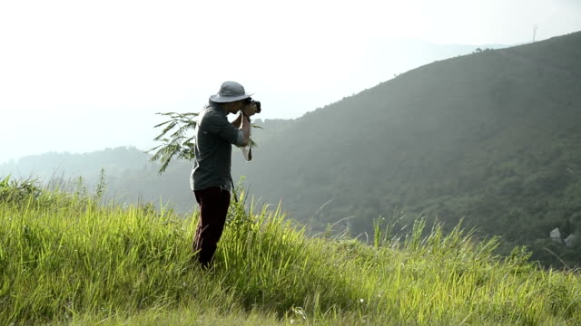 nature photographer in action - slr camera stock videos and b-roll footage