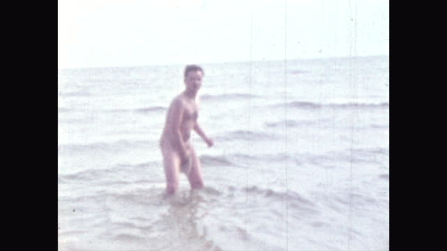 naturism at the Baltic Sea in the GDR Eastern Germany German democratic Republic naturists taking a bath jumping into the sea naked at the beach
