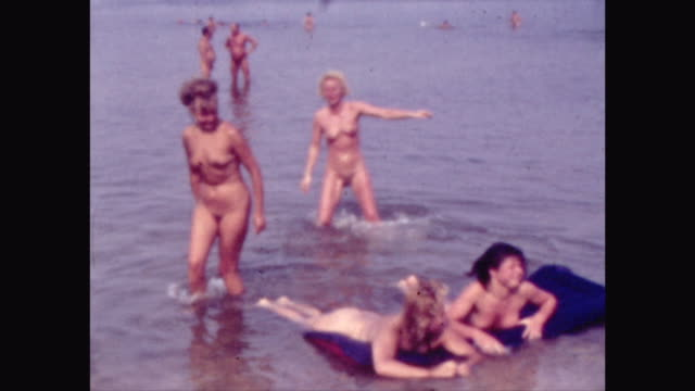 naturism at the Baltic Sea in the GDR Eastern Germany German democratic Republic naturists taking a bath jumping into the sea at the beach...