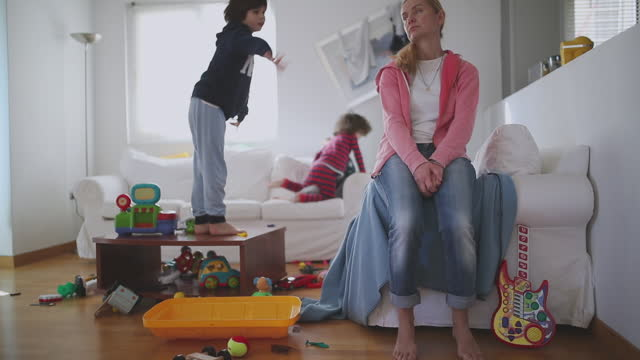 naughty kids jumping to sofa and her mother looking tired - chaos stock-videos und b-roll-filmmaterial