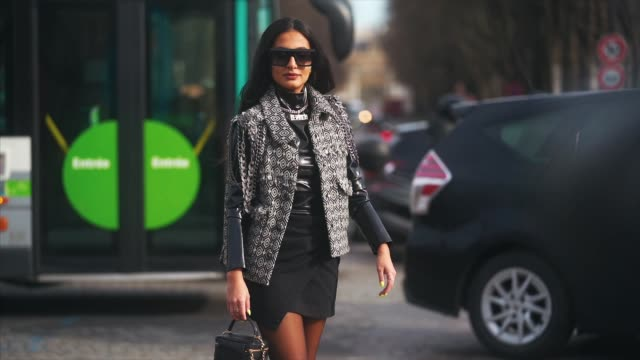 nausheen shah wears sunglasses, a jacket with printed geometric patterns, a black leather top, a necklace, a black skirt, a quilted bag, tights,... - tights stock videos & royalty-free footage