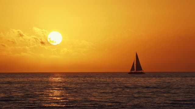 Nautical vessel sailing against golden sunset