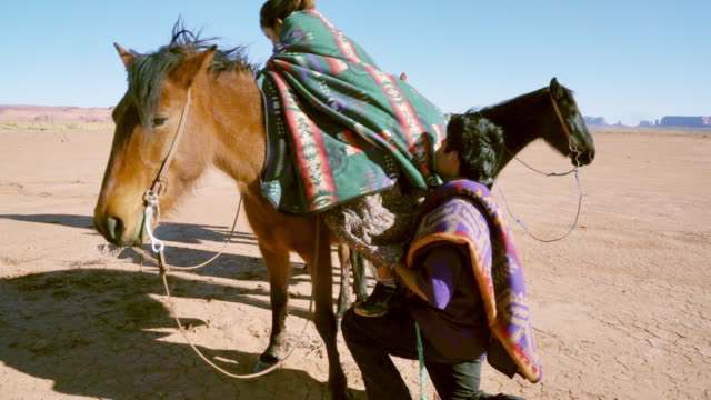 navajo brother being a gentleman, helping his young sister on her horse - utah stock videos & royalty-free footage