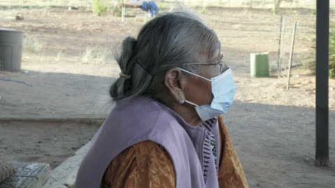 navajo grandma in her 80s sitting in front of her house in monument valley arizona wearing a face mask to prevent contracting the corona or covid-19 virus - puebloan culture stock videos & royalty-free footage