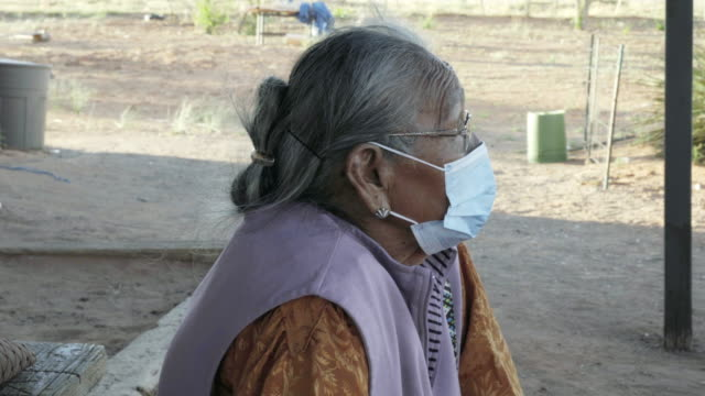 navajo grandma in her 80s sitting in front of her house in monument valley arizona wearing a face mask to prevent contracting the corona or covid-19 virus - navajo culture stock videos & royalty-free footage