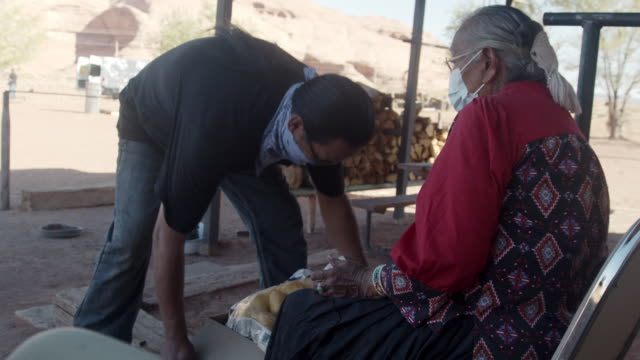 vídeos de stock e filmes b-roll de a navajo man living on the navajo reservation in monument valley delivers a box of food to an elderly navajo woman during covid-19 - esfomeado