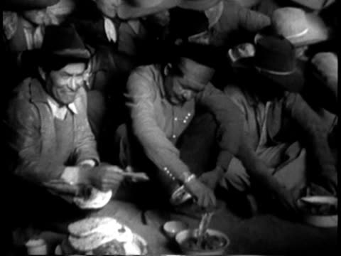 1939 MONTAGE MS Navajo men and women enjoying a traditional meal in Navajo hogan / Southwest United States / AUDIO