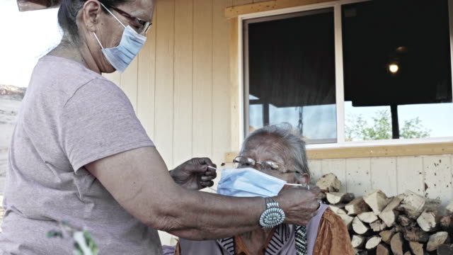 a navajo woman assisting her mother with a face mask to protect her from coronavirus - navajo culture stock videos & royalty-free footage