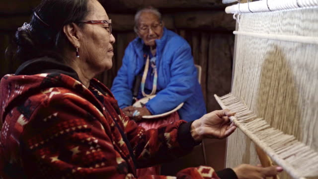 a navajo woman weaves a saddle blanket on a loom, her mother in the background - north american tribal culture stock videos & royalty-free footage
