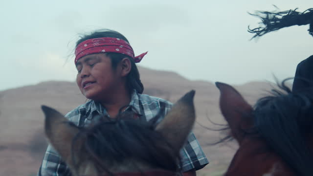 乗馬に行く準備をしているヘッドバンドを身に着けている彼の馬に裸で座っているナバホヤングボーイズ - ナバホ文化点の映像素材/bロール