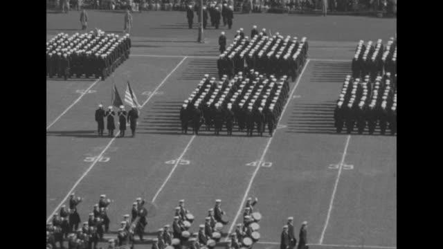 naval academy midshipmen march in formation onto football field at municipal stadium / midshipmen walk past / military band plays as midshipmen... - 士官候補生点の映像素材/bロール