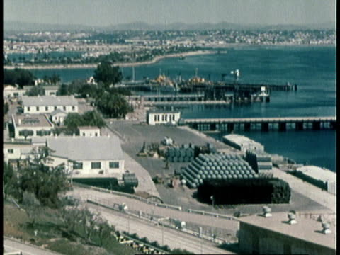1960 MONTAGE HA naval base along coastline, man in hard had working on pipes, PAN electric power system, VO corrosion for the navy is a never ending problem / United States