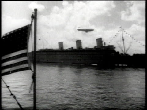 vidéos et rushes de us naval battleship with barrage balloon overhead and us flag in foreground / aerial ship's deck with massed soldiers - plan grue