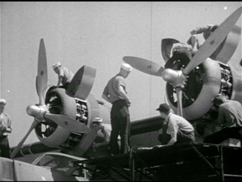 vídeos de stock, filmes e b-roll de naval consolidated pby catalina flying boats aircraft parked on tarmac vs us navy mechanics technicians working on aircraft tightening bolt by hand... - 1943