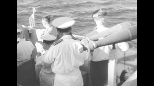 stockvideo's en b-roll-footage met naval officers on boat stationary binoculars behind one ocean to side two turn around to look through binoculars / crowd of british and australian... - kernbom