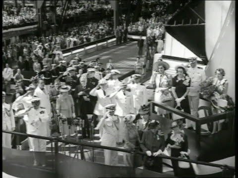 vidéos et rushes de naval officers standing on dock saluting woman standing near railing crowd bg ha ws large ship being launched sliding toward water no name visible no... - marin